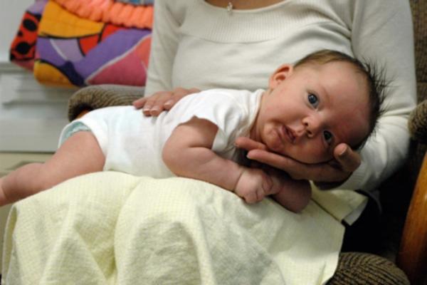 Burping baby lying across knees